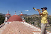 San Juan Teitipac, Oaxaca, Mexico Man playing a bugle on the roof of the 16th century Dominican church in a small Zapotec town - Jim West - 2010s,2018,ACE,architecture,Arts,BAME,BAMEs,Belief,BME,bmes,bugle,bugler,buildings,Catholic,Catholics,christian,christianity,christians,church,churches,conviction,Culture,diversity,Dominican,Dominican