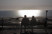 Couple sitting on a bench on a Spring evening watching the sea, Blackpool promenade - Stefano Cagnoni - 2010s,2018,adult,adults,bench,COAST,Couple,COUPLES,evening,FEMALE,glisten,glistening,leisure,LFL,LIFE,lifestyle,male,man,men,OCEAN,people,person,persons,promenade,recreation,RECREATIONAL,reflection,re