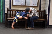 Tired couple, St James Park underground station around 9pm on a weekday - Stefano Cagnoni - 2010s,2018,adult,adults,alcohol,asleep,bench,boyfriend,BOYFRIENDS,care,caring,cities,City,comforting,couple,COUPLES,Drunken Stupor,empathy,EXHAUSTION,FEMALE,girlfriend,journey,journeys,Leisure,LFL,LIF