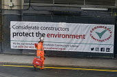 Construction worker carrying Leica Builder 100 Theodolite equipment on building site, Waterloo London. Considerate constructors protect the environment banner - Stefano Cagnoni - 20-03-2018