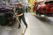 Jaguar Land Rover factory, Solihull. Woman assembly worker sweeping the floor whilst the production line has halted - John Harris - 2010s,2017,assembly,AUTO,AUTOMOBILE,AUTOMOBILES,automotive,broom,brooms,car,Car Industry,carindustry,cars,EBF,Economic,Economy,employee,employees,Employment,engineer,engineers,FACTORIES,factory,FEMALE