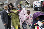 Sadiq Khan selfie with a family going to church, Labour Party local election campaign, Earlsfield ward, Wandsworth, London - Jess Hurd - 2010s,2018,adult,adults,BAME,BAMEs,Black,BME,bmes,CAMERA,camera phone,cameras,campaign,campaigning,CAMPAIGNS,candidate,candidates,CANVASING,canvassing,child,CHILDHOOD,children,church,churches,cities,C