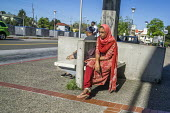 Oakland, California, USA: Asian woman waiting for a bus connection to the Bay Area Rapid Transit - David Bacon - 2010s,2018,adult,adults,american,americans,Asian,Asians,BAME,BAMEs,Bangladeshi,Bangladeshis,BART,Black,BME,bmes,bored,boredom,boring,bus,bus service,Bus Stop,buses,California,cities,City,commute,commu