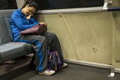 San Francisco, California, USA: Passenger asleep on the Bay Area Rapid Transit train between San Francisco and Oakland as they go through the tunnel beneath San Francisco Bay - David Bacon - 2010s,2018,adult,adults,american,americans,Asian,Asians,asleep,bag,bags,BAME,BAMEs,BART,BME,bmes,California,carriage,carriages,cities,City,COMMUTE,commuter,commuters,commuting,Diaspora,diversity,EARNI