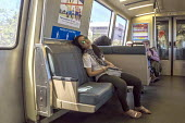 San Francisco, California, USA: Passenger asleep on the Bay Area Rapid Transit train between San Francisco and Oakland - David Bacon - 2010s,2018,adult,adults,american,americans,asleep,BART,California,carriage,carriages,cities,City,commute,commuter,COMMUTERS,COMMUTING,EBF,Economic,Economy,exhausted,exhaustion,FEMALE,journey,JOURNEYS,