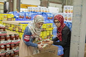 Novi, Michigan, USA: Muslim volunteers packing food boxes for the poor in the Detroit during the holy month of Ramadan - Jim West - 2010s,2018,America,american,americans,Belief,box,boxes,charitable,charity,cities,City,community service,conviction,Detroit,Diaspora,donated,donation,donations,dress,excluded,exclusion,faith,FEMALE,foo