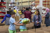 Novi, Michigan, USA: Muslim volunteers packing food boxes for the poor in the Detroit during the holy month of Ramadan - Jim West - 2010s,2018,America,american,americans,Belief,box,boxes,boy,boys,charitable,charity,child,CHILDHOOD,children,cities,City,community service,conviction,Detroit,Diaspora,donated,donation,donations,exclude