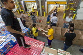 Novi, Michigan, USA: Muslim volunteers packing food boxes for the poor in the Detroit during the holy month of Ramadan - Jim West - 2010s,2018,America,american,americans,Belief,box,boxes,charitable,charity,cities,City,community service,conviction,Detroit,Diaspora,donated,donation,donations,excluded,exclusion,faith,food,food aid di