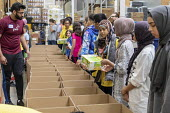 Novi, Michigan, USA: Muslim volunteers packing food boxes for the poor in the Detroit during the holy month of Ramadan - Jim West - 2010s,2018,America,american,americans,Belief,box,boxes,charitable,charity,child,CHILDHOOD,children,cities,City,community service,conviction,Detroit,Diaspora,donated,donation,donations,dress,excluded,e