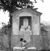 Mother and her child resting beneath a roadside shrine to the Madonna and child Tuscany, Italy 1958 - Romano Cagnoni - 13-05-1958