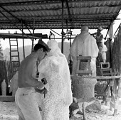 Stonemason wearing traditional hat made from newspaper working on marble, workshop near Pietrasanta, Tuscany, Italy 1958 - Romano Cagnoni - 13-05-1958