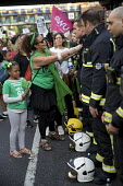 Local community thanking the firefighters. Silent march in memory of the victims of Grenfell Tower fire on the first anniversary, Kensington, London - Jess Hurd - 1st,2010s,2018,activist,activists,adult,adults,anniversary,BAME,BAMEs,Black,Black and White,BME,bmes,CAMPAIGNING,CAMPAIGNS,child,CHILDHOOD,children,COMMEMORATE,commemorating,commemoration,COMMEMORATIO