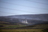 Helicopter dropping water onto Saddleworth Moor fire, Stalybridge, Derbyshire. Provided by water firm United Utilities it is being used to collect water from a nearby reservoir and drop it on the moor... - Jess Hurd - 28-06-2018