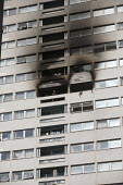 Firefighter looks out from a window of Grafton House where a twelfth floor fire is contained and brought under control by over 50 firefighters at a 22 story East End Homes tower block in Mile End, Eas... - Jess Hurd - 29-06-2018