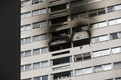 Firefighter looks out from a window of Grafton House where a twelfth floor fire is contained and brought under control by over 50 firefighters at a 22 story East End Homes tower block in Mile End, Eas... - Jess Hurd - 2010s,2018,22 story,accident,accidental,accidents,adult,adults,block,blocks,building,buildings,cities,City,damage,damaged,destroyed,destruction,DIA,Disaster,disasters,East,East End Homes,fire,fire bri