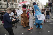 Media with two dinosaurs, Russian TV reporting Together Against Trump marching against the visit to the UK of Donald Trump, London. - Jess Hurd - 13-07-2018
