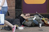 Homeless youth sleeping in the street during a heatwave, Stratford Upon Avon, Warwickshire - John Harris - 2010s,2018,asleep,bag,bags,doorway,excluded,exclusion,exhausted,exhaustion,guitar,guitars,HARDSHIP,heat,homeless,homelessness,hot,impoverished,impoverishment,INEQUALITY,male,man,Marginalised,men,music
