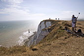 Tourists taking selfies, Beachy Head, a Chalk headland and suicide spot in East Sussex - Jess Hurd - 2010s,2018,adult,adults,amateur,attraction,Beachy Head,Chalk,cliff,cliffs,COAST,coastal,coasts,committed,committing,country,countryside,couple,COUPLES,East Sussex,edge,eroded,erosion,FEMALE,headland,h