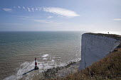 Tourists at Beachy Head, a Chalk headland and suicide spot in East Sussex. Beachy Head Lighthouse - Jess Hurd - 2010s,2018,attraction,Beachy Head,Chalk,cliff,cliffs,COAST,coastal,coasts,committed,committing,country,countryside,East Sussex,edge,eroded,erosion,FEMALE,headland,height,high up,holiday,holiday maker,