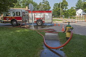 Parchment, Michigan USA, State of emergency declared after high levels of PFAS chemicals found in drinking water. Fire engine pumping water from a Kalamazoo fire hydrant down the street to connect wit... - Jim West - 2010s,2018,America,chemical,chemical contamination,chemical exposure,chemicals,cities,City,clean water,connection,contaminated,contamination,drink,drinking,drinking water,emergency,engine,ENGINES,ENI,