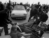 Police removing women blockading Red Gate RAF Greenham Common 1983 against USAF Cruise Missiles, Berkshire - John Harris - peace movement,1980s,1983,activist,activists,adult,adults,against,airforce,Anti War,Antiwar,armed forces,arrest,arrested,arresting,AUTO,AUTOMOBILE,AUTOMOBILES,AUTOMOTIVE,block,blockade,blockading,bloc