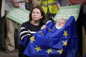 Pro EU People's Vote rally, Newcastle Upon Tyne, mother with child wrapped in EU Flag. Campaigning for a public vote on the final Brexit deal between the UK and the European Union - Mark Pinder - 2010s,2018,adult,adults,babies,baby,Brexit,campaign,campaigning,CAMPAIGNS,CHILD,CHILDHOOD,CHILDREN,democracy,democrat,EARLY YEARS,EU,European Union,families,FAMILY,FEMALE,flag,flags,future hope,hopes,