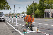 Detroit, Michigan USA Workers installing bicycle lanes on a busy street. The city is dramatically expanding protected bicycle lanes, from less than 10 miles a decade ago to more than 125 miles in 2018 - Jim West - 2010s,2018,America,american,americans,barrier,bicycle,bicycle lane,bicycle lanes,bicycle riding,BICYCLES,BICYCLING,Bicyclist,Bicyclists,BIKE,bike lanes,bike riding,BIKES,bollard,bollards,BUILDING,busy