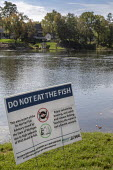 Michigan USA: Sign warning anglers Do not Eat The Fish, Huron River, Central Park, Milford. High levels of carcinogenic PFAS chemicals have been found in the water. PFAS are widely used many products.... - Jim West - 2010s,2018,Agency,America,american,americans,birth,cancer,CANCERS,capitalism,carcinogen,carcinogenic,chemical,chemical contamination,chemicals,child,children,clean water,contaminated water,contaminati