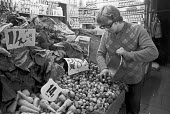 Shopkeeper weighing out vegetables in a local shop, London 1976 - NLA - 1970s,1976,convenience store,Corner Shop,EBF,Economic,Economy,employee,employees,Employment,job,jobs,keepers,LBR,local,local shop,London,Low Pay,outlet,outlets,people,potato,potatoes,shop,shop keeper,