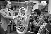 Blowing the tuba. School pupils get the chance to play with the instruments of the orchestra, London 1978 - NLA - 1970s,1978,ACE,Arts,BAME,BAMEs,Black,Black and White,BME,bmes,child,CHILDHOOD,children,Culture,diversity,EDU,educate,educating,Education,educational,ethnic,ethnicity,juvenile,juveniles,kid,kids,knowle