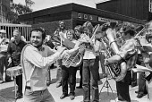 Kenny Everett on picket line during MU BBC strike, 1980 against cut to 5 inhouse orchestras - NLA - 1980,1980s,against,bands,BBC,Brass Band,disc jocky,DISPUTE,disputes,Industrial dispute,Kenny Everett,melody,member,member members,members,MU strike,music,MUSICAL,musical instrument,musical instruments