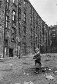 Boy playing with rusty frying pan in courtyard, Glasgow tenement 1971 - Martin Mayer - 1970s,1971,blocks,boy,boys,child,CHILDHOOD,children,cities,City,excluded,exclusion,Glasgow,HARDSHIP,home,homes,HOUSING,Housing Estate,impoverished,impoverishment,INEQUALITY,juvenile,juveniles,kid,kids