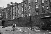 Boy playing with rusty frying pan in courtyard, Glasgow tenement 1971 - Martin Mayer - 23-06-1971