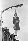Effigy of Margaret Thatcher hanging from a lamp post, Brixton, London 1980 - Peter Arkell - 1980,1980s,activist,activists,against,anger,angry,CAMPAIGNING,CAMPAIGNS,CONSERVATIVE,Conservative Party,conservatives,cut out,cutout,DEMONSTRATING,Demonstration,effigy,EMOTION,EMOTIONS,FEMALE,figure,f