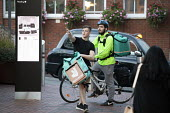 Deliveroo worker, Shopping Centre, Reading, Berkshire - John Harris - 2010s,2018,assisting,backpack,bicycle,bicycles,BICYCLING,Bicyclist,Bicyclists,BIKE,BIKES,buying,by hand,carries,carry,carrying,cities,city,collecting,commodities,commodity,consumer,consumers,contracts