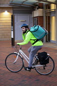 Deliveroo worker, Shopping Centre, Reading, Berkshire - John Harris - 2010s,2018,backpack,bicycle,bicycles,BICYCLING,Bicyclist,Bicyclists,BIKE,BIKES,buying,by hand,call,calls,carries,carry,carrying,CELLULAR,cities,city,collecting,commodities,commodity,communicating,comm