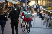Deliveroo worker, Shopping Centre, Reading, Berkshire - John Harris - 2010s,2018,backpack,bicycle,bicycles,BICYCLING,Bicyclist,Bicyclists,BIKE,BIKES,buying,by hand,carries,carry,carrying,cities,city,collecting,commodities,commodity,consumer,consumers,contracts,Courier,C