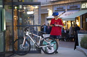 Deliveroo worker, Shopping Centre, Reading, Berkshire - John Harris - 2010s,2018,app,application,applications,apps,backpack,bicycle,bicycles,BICYCLING,Bicyclist,Bicyclists,BIKE,BIKES,buying,by hand,call,calls,carries,carry,carrying,catering,CELLULAR,cities,city,collecti