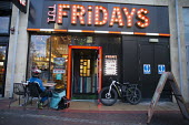 Deliveroo worker, Shopping Centre, Reading, Berkshire. Collecting from TGI Friday. Waiting for the take away - John Harris - ,2010s,2018,backpack,bicycle,bicycles,BICYCLING,Bicyclist,Bicyclists,BIKE,BIKES,buying,by hand,carries,carry,carrying,catering,cities,city,collecting,collection,commodities,commodity,consumer,consumer