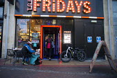 Deliveroo worker, Shopping Centre, Reading, Berkshire. Collecting from TGI Fridays - John Harris - ,2010s,2018,app,application,applications,apps,backpack,bicycle,bicycles,BICYCLING,Bicyclist,Bicyclists,BIKE,BIKES,buying,by hand,carries,carry,carrying,catering,cities,city,collecting,collection,commo