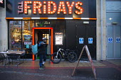 Deliveroo worker, Shopping Centre, Reading, Berkshire. Collecting from TGI Fridays - John Harris - ,2010s,2018,backpack,bicycle,bicycles,BICYCLING,Bicyclist,Bicyclists,BIKE,BIKES,buying,by hand,carries,carry,carrying,catering,cities,city,collecting,collection,commodities,commodity,consumer,consumer