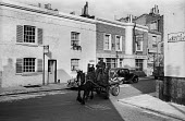 Rag 'n' Bone Man riding a horse and cart through Chelsea streets 1958 with little girl on the back of the cart eating an ice cream - Alan Vines - 1950s,1958,animal,animals,barrow,Billing Street,cart,Chelsea. parked cars,child,CHILDHOOD,children,cities,City,collecting,collection,Domesticated Ungulates,driver,drivers,driving,eating,EBF,Economic,E