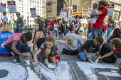 Oakland, California, USA- Hotel workers strike against low pay at the Marriott City Center Hotel sit down blocking the road, children painting the strike slogan, One Job Should be Enough, on the road... - David Bacon - 20-10-2018