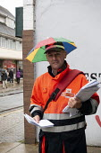 Postal worker with umbrella hat delivering the post, Stratford-upon-Avon, Warwickshire - John Harris - 06-10-2018