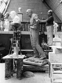 Sculptor David McFall working on his statue of Sir Winston Churchill, Chelsea, London 1958. The sculpture is to to be cast in bronze and placed at the edge of Epping Forest in Churchill's constituency... - Alan Vines - 1950s,1958,ACE,art,artist,artist studio,artists,arts,artwork,artworks,bust,carving,cities,City,culture,David McFall,Forest,London,model,models,plaster,sculpting,sculptor,sculpture,SCULPTURES,Sir Winst