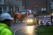 Workers laying tarmac road on a housing estate, Rugeley, Staffordshire - John Harris - 2010s,2018,application,applied,applying,cold,Construction Industry,Contractor,Contractors,course,driver,drivers,driving,dusk,EBF,Economic,Economy,employee,employees,Employment,evening,highway,housing,