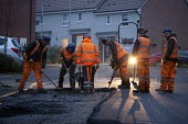 Workers laying tarmac road on a housing estate, Rugeley, Staffordshire - John Harris - 2010s,2018,application,applied,applying,cold,Construction Industry,Contractor,Contractors,course,drill,drilling,dusk,EBF,Economic,Economy,employee,employees,Employment,evening,hard hat,hard hats,highw