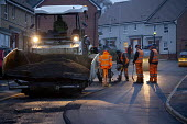 Workers laying tarmac road on a housing estate, Rugeley, Staffordshire - John Harris - 2010s,2018,application,applied,applying,cold,Construction Industry,Contractor,Contractors,course,drill,drilling,driver,drivers,driving,dusk,EBF,Economic,Economy,employee,employees,Employment,evening,h