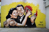 Mural by Art SRX, A 1950s couple light a Coca Cola molotov cocktail, Custard factory, Birmingham - John Harris - 2010s,2018,adult,adults,Birmingham,bottle,bottles,Cola,couple,COUPLES,FACTORIES,factory,FEMALE,graffiti,lighter,lighting,male,man,men,Molotov Cocktail,mural,MURALS,Painting,paintings,people,person,per