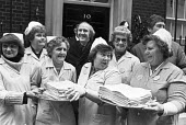 Dinner ladies from Lincoln presenting a petition, 10 Downing Street, 1981 calling on the government to stop the cuts and save the school dinner service - NLA - 1980s,1981,activist,activists,against,CAMPAIGNING,CAMPAIGNS,cuts,DEMONSTRATING,Demonstration,Dinner,dinners,GMWU,government,Lincoln,London,member,member members,members,NUPE,people,petition,PETITIONIN